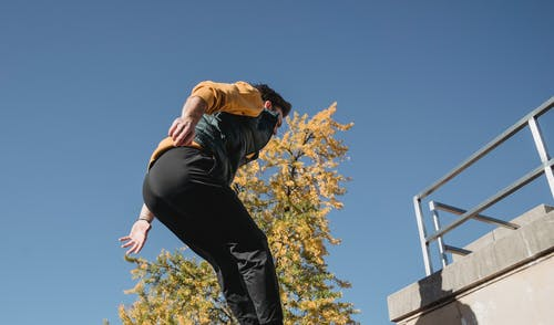 From below of determined male athlete jumping high while training on urban building