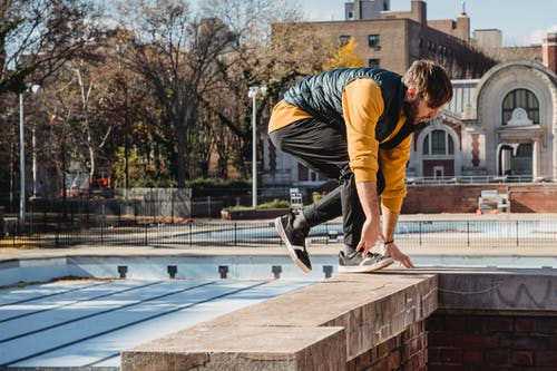 Side view of focused male athlete in activewear preparing for stunt on brick building