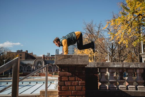 Side view of male athlete in activewear performing handstand while jumping on roof of building