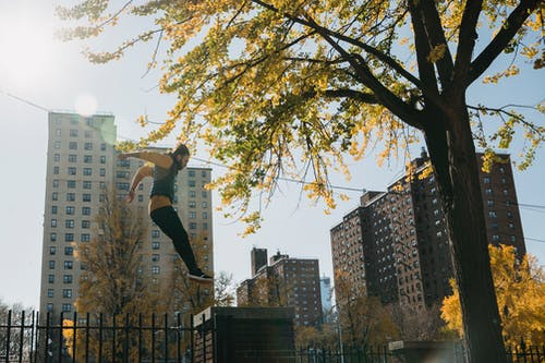 Low angle of energetic male athlete performing tricks on height while training in sunny autumn