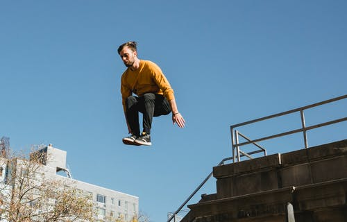 Low angle of young male athlete performing parkour jump on building under clear blue sky