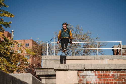 Full body of concentrated male athlete performing stunt on brick building while training outdoors