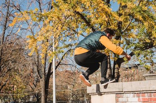 Unrecognizable sportsman jumping on brick border