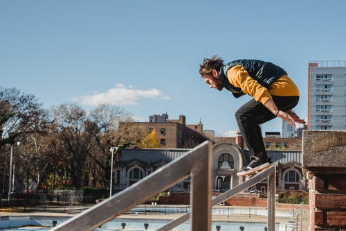 Full body of focused male athlete in sneakers practicing parkour stunts on urban building