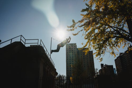 Silhouette of anonymous male athlete performing trick while practicing parkour under bright sunlight