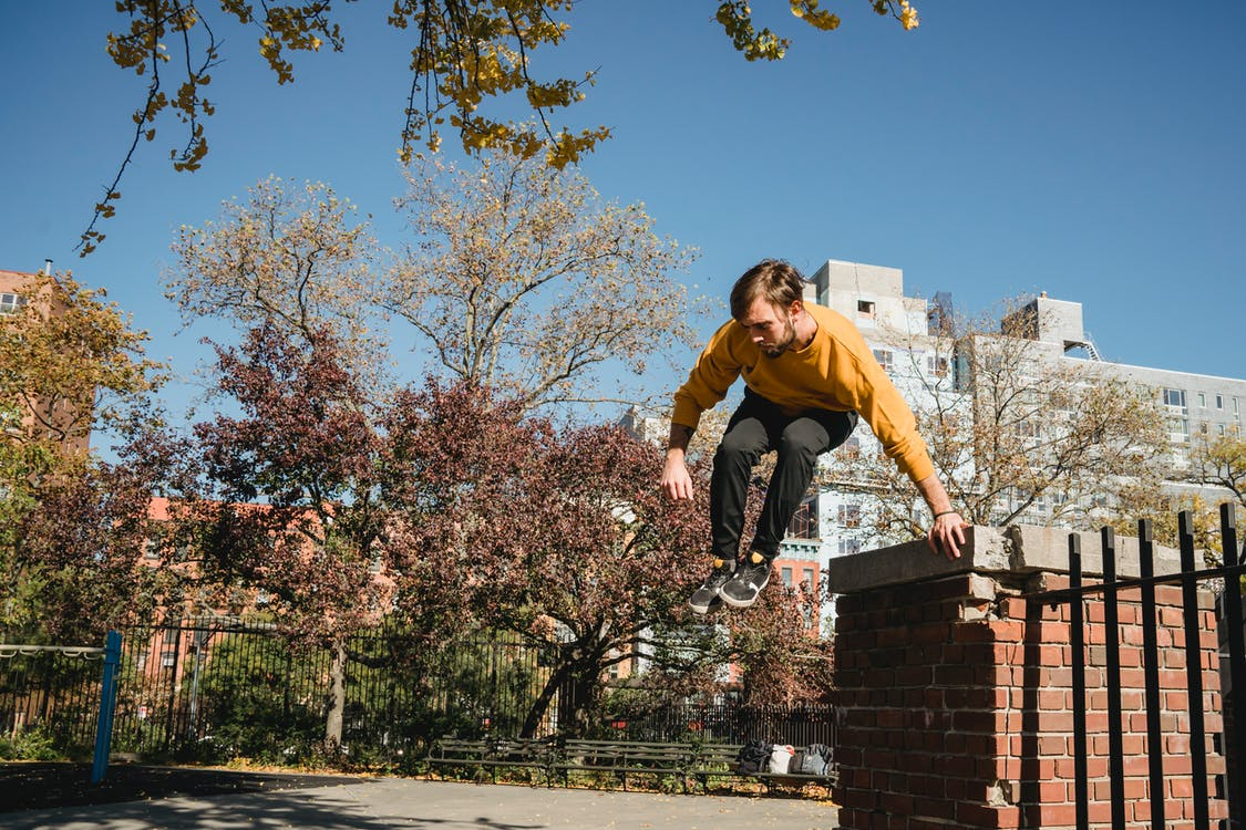 From below full body of young guy in casual clothes doing parkour jump in park in sunny autumn weather