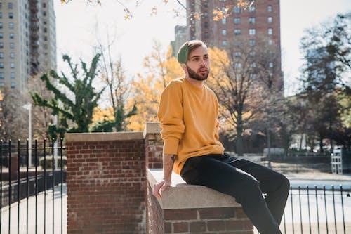 Man sitting on brick fence on street
