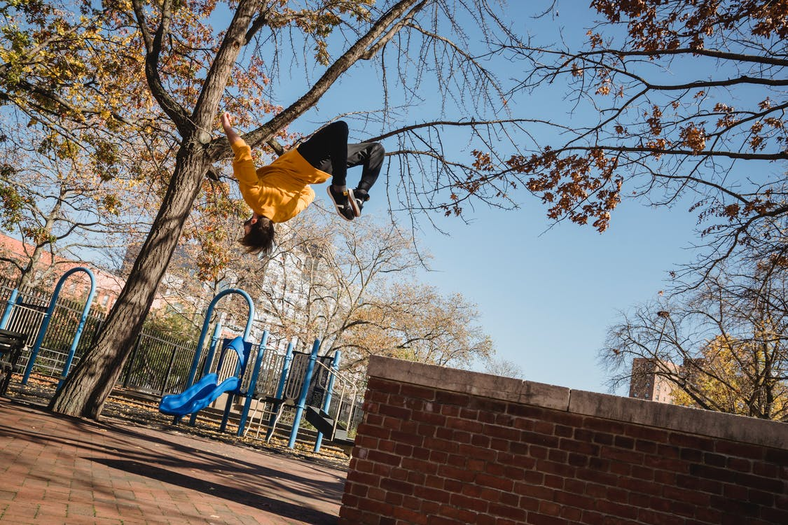 From below full length of faceless young male wearing casual clothes and jumping from fence while doing parkour stunts in city street in autumn day