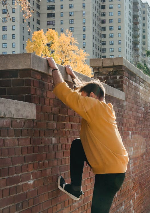Faceless male tracer climbing brick fence in park