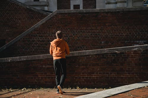Back view full length male wearing casual clothes standing near massive brick construction on sunny day