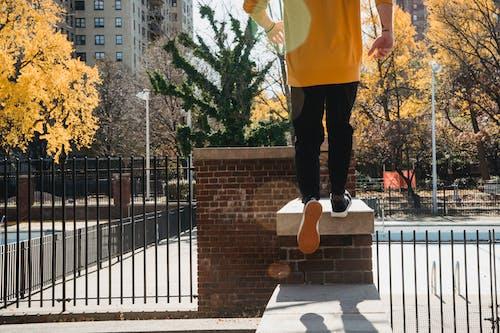 Crop faceless man running on brick fence in city park