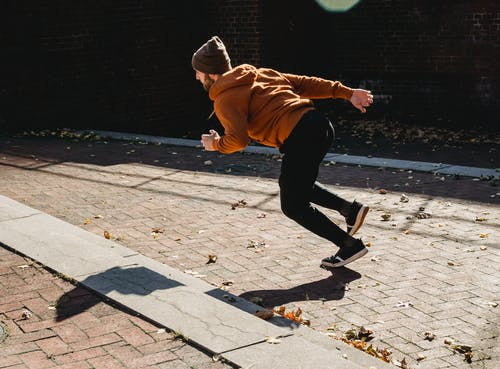 Energetic faceless man running on pavement