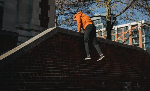 Back view full length energetic male tracer climbing over brick fence in modern town on sunny autumn day