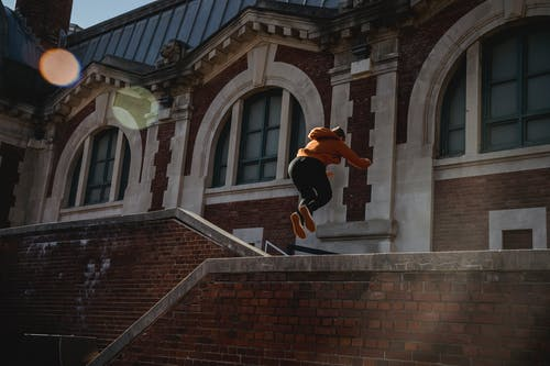 Unrecognizable person jumping over brick building parapet