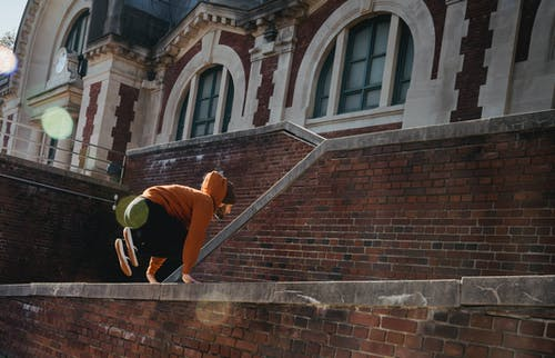 Side view full length male tracer wearing hoodie jumping over brick building parapet and practicing parkour on clear day