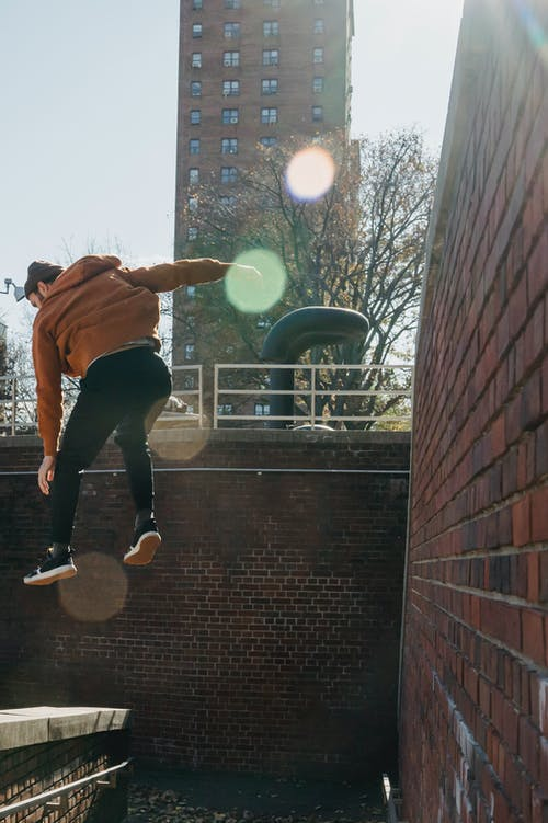 Faceless man jumping from brick wall in sunny town