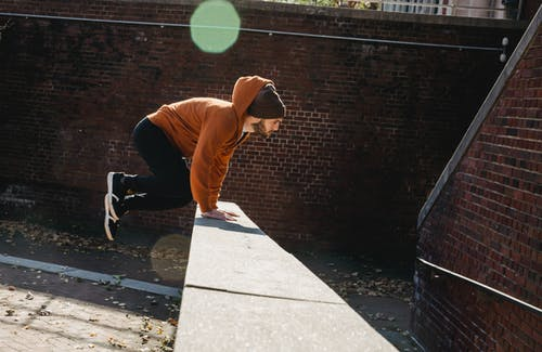 Side view full body energetic young male tracer in hoodie and hat jumping over barrier against brick wall on sunny autumn day