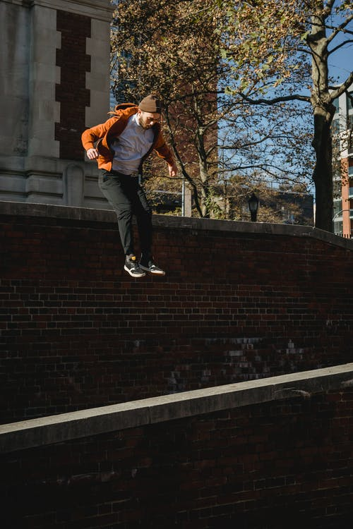 Fit man jumping from brick wall in sunny town