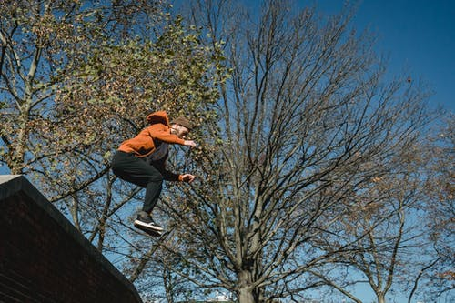 Energetic man jumping from brick wall in park