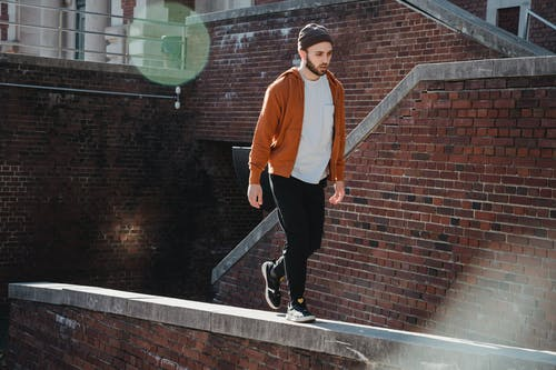 Full body young concentrated male in casual wear walking on narrow parapet of brick building on sunny day