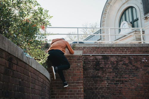 Unrecognizable man climbing brick building wall