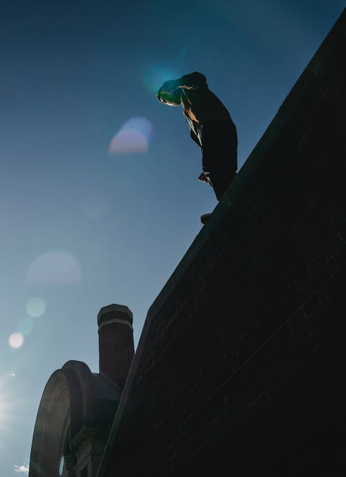 From below slim male silhouette standing on tall brick wall against blue sky on sunny weather