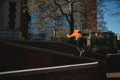 Unrecognizable man jumping from brick barrier in city park
