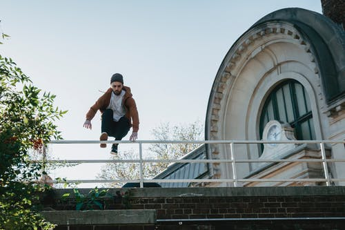 Young man jumping over railing on building roof