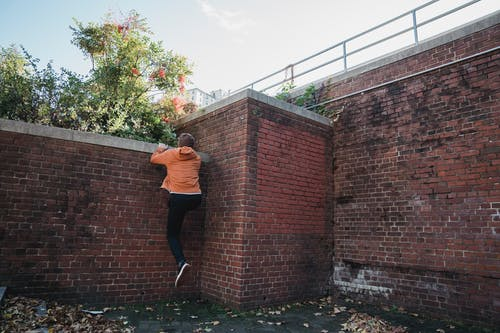 Faceless energetic man climbing brick wall