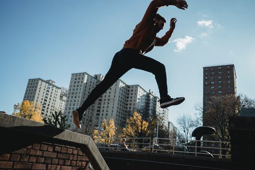 Fit man jumping from brick parapet in urban city