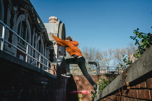 Unrecognizable man jumping above steps of brick building