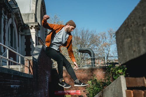 Sporty man jumping from brick building railing