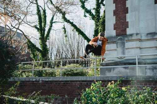 Sporty man jumping over railing near brick building