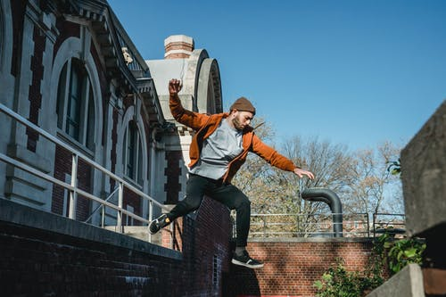 Energetic man jumping from wall in town