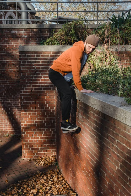 Side view full body of bearded determined male climbing on wall while doing parkour in urban area
