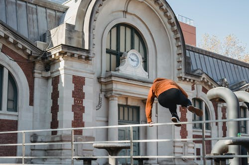 Sportive man jumping over railing near old historic building