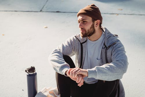 Bearded sportsman resting on street with clasped hands after exercising