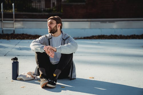 Thoughtful sportsman resting on city pavement after working out