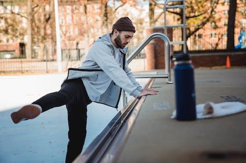 Determined sportsman warming up near urban platform