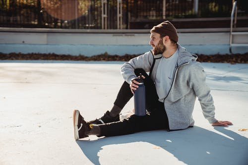 Young hipster male athlete in informal outfit sitting with bottle on urban pavement while looking away