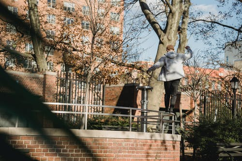Back view of male in casual clothes walking on top of metal fence of brick construction on city street in residential district in sunny day