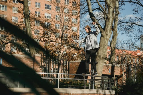 Male balancing on railing in park near buildings in town
