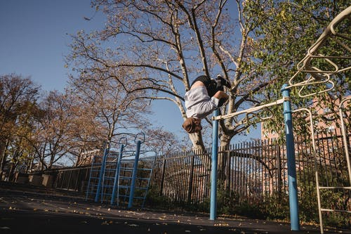 From below full body of unrecognizable male doing parkour while backflip in park near metal turnstile in street in sunny autumn day near trees with fence under blue cloudless sky