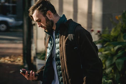 Guy using phone in city street