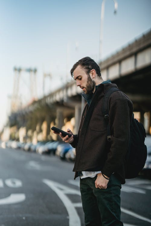 Side view of serious young man in casual clothes standing on asphalt road while text messaging on phone near cars and bridge in city street in daytime