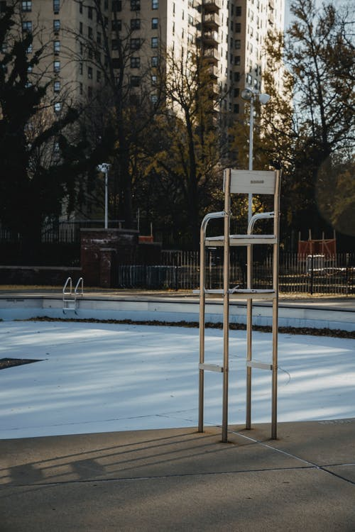 Metal chair at empty pool on sport ground