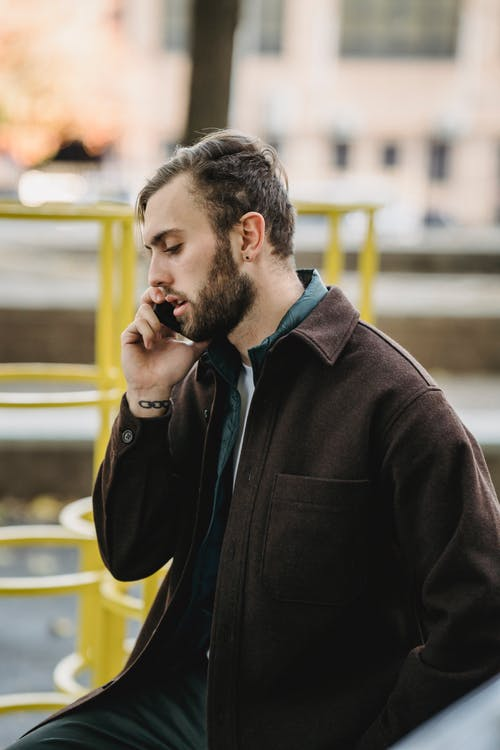 Side view of young bearded man in suede jacket talking on smartphone on playground