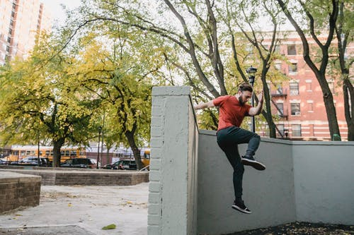Full body side view of young man in sportswear performing parkour trick on while jumping off concrete border in street