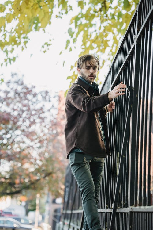 Stylish young man holding to metal fence