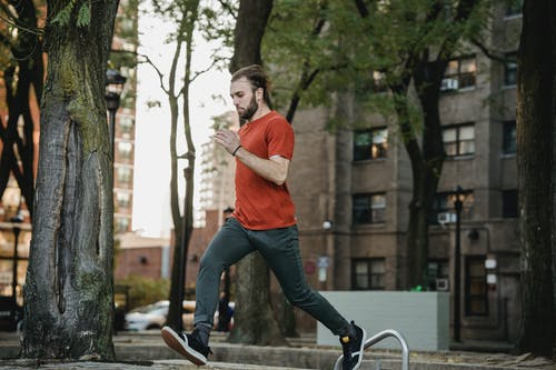 Bearded sportsman running on urban stairs during training